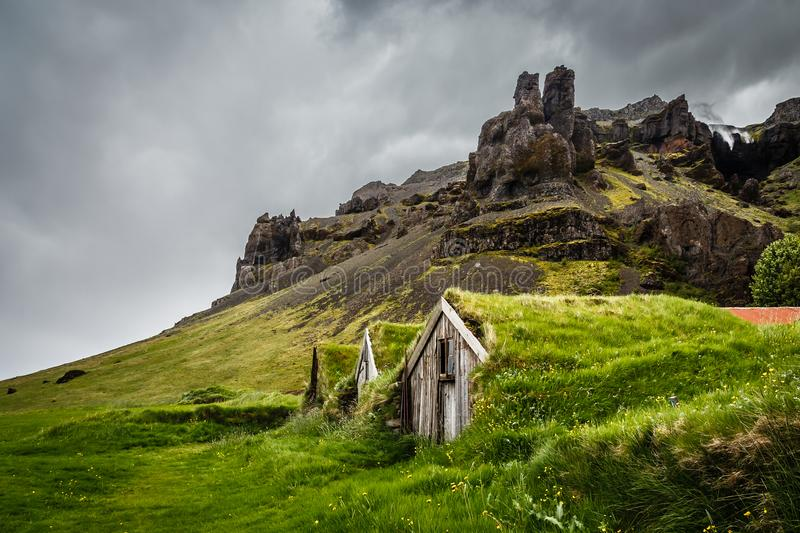 Icelandic turf houses covered with grass and cliffs in the background near Kalfafell vilage, South Iceland royalty free stock photo