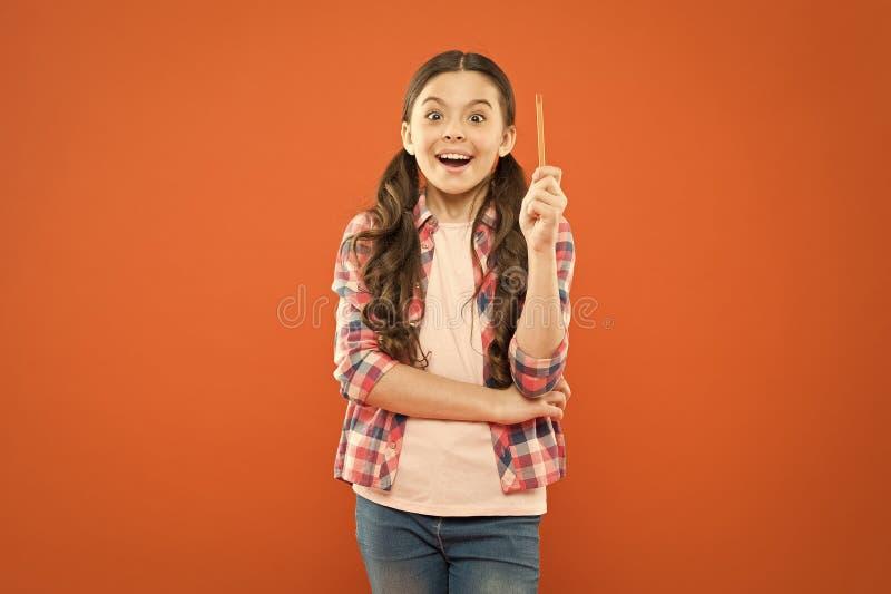 Ich bin das Genie Girl Genie Genius kleines Schulmädchen bekam eine helle Idee auf orangefarbenem Hintergrund Kleiner Kinderzeige lizenzfreie stockbilder