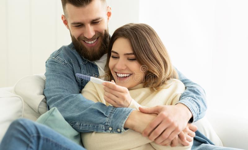 Ich bin schwanger! Glückliches Paar, das Schwangerschaftstest überprüft lizenzfreies stockfoto