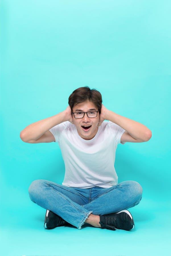 Ich bin Sie bin hier so gl?cklich Atelieraufnahme des attraktiven spielerischen asiatischen Mannes, sitzend auf Boden mit dem gek lizenzfreie stockfotografie