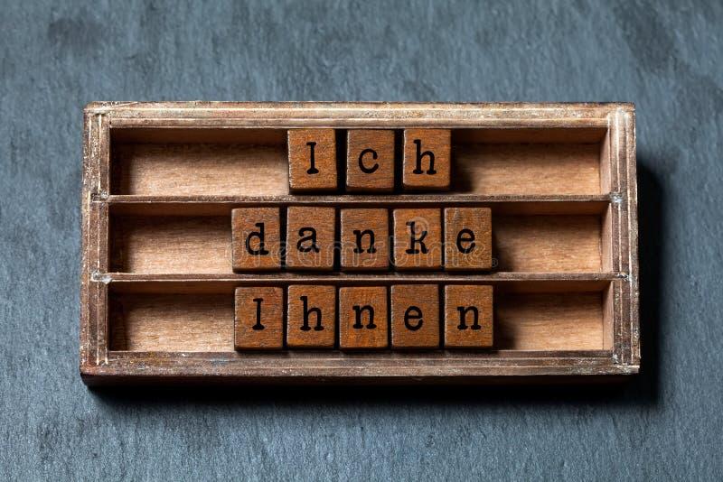 Ich danke Ihnen Tacka dig i tysk översättning Tappningask, tacksamt uttrycksmeddelande för träkuber som är skriftligt med gammalt fotografering för bildbyråer