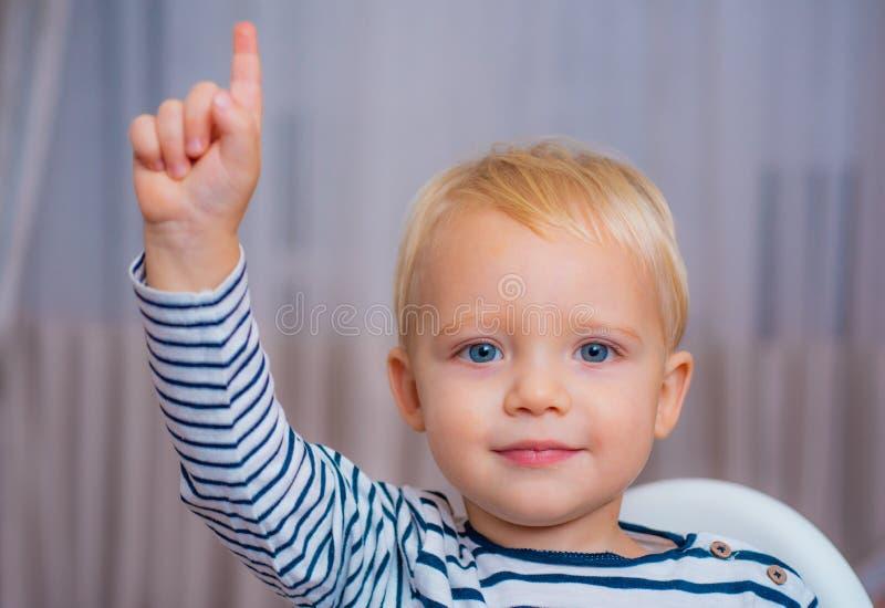 Ich habe ausgezeichnete Idee Blaue Augen des netten Kleinkindes des Jungen, die aufwärts Zeigefinger zeigen Kreatives Ideen-Konze stockfotografie