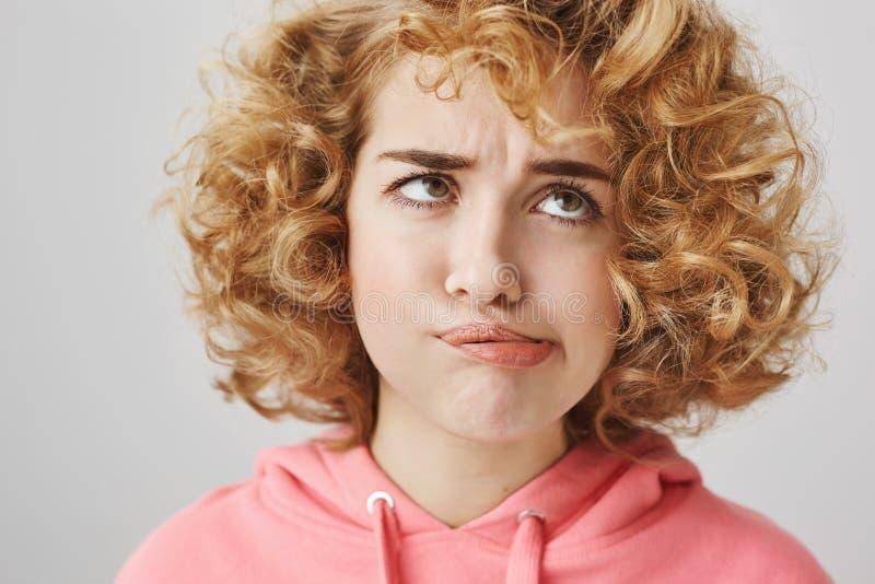 Ich hasse meine Locken Schöne lustige kaukasische gelockte jammernde Frau beim Versuchen, Haar von der Stirn wegzublasen stockfotos