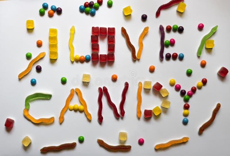 Ich liebe den Süßigkeitssatz, der aus verschiedenen bunten Bonbons heraus auf weißem Hintergrund gemacht wird stockfotografie