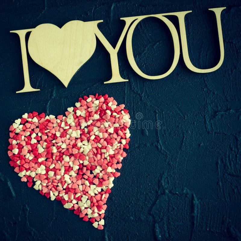 Ich liebe dich - hölzerne Phrase auf schwarzem Steinhintergrund stockfotografie
