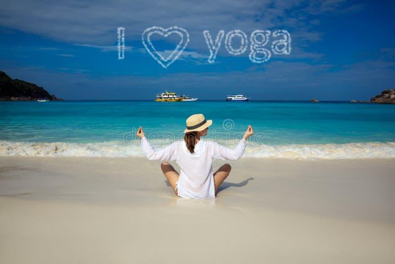 Ich liebe Yoga Junge Frau, die in Lotus Pose auf tropischem Strand meditiert lizenzfreie stockfotografie
