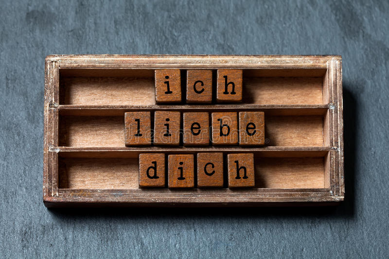 Ich liebedich Jag älskar dig i tysk översättning Tappningask, träkubuttryck som är skriftligt med bokstäver för gammal stil grått royaltyfri fotografi
