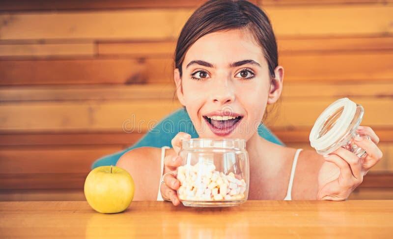 Ich wünsche sie alle Hübsche Frau bevorzugen Eibische gegenüber Apfel Frau wählen, welche Nahrung zu essen E lizenzfreie stockfotos