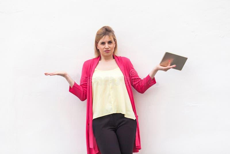 Ich weiß nicht! Porträt der schuldigen jungen erwachsenen Frau in der rosa Bluse und schwarzen in den Hosen, die mit den angehobe lizenzfreie stockbilder
