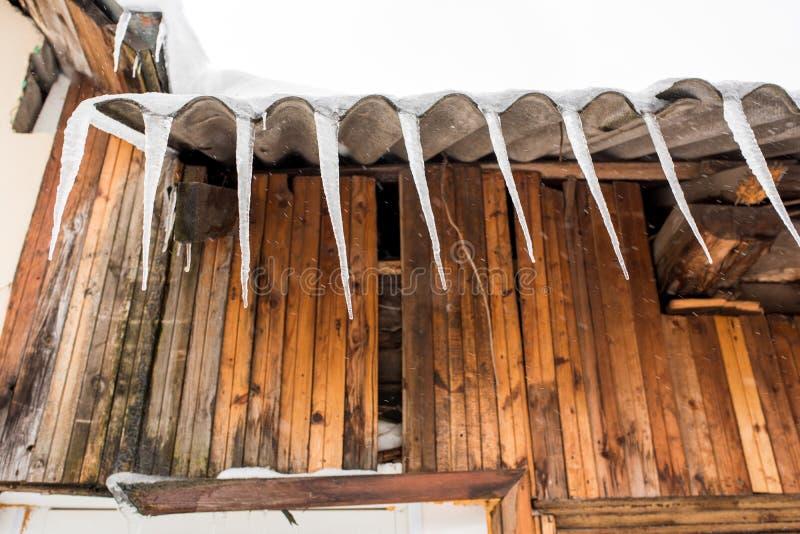 Icicle appese dal tetto di una casa di legno in campagna, in una giornata gelida e nuvolosa fotografia stock