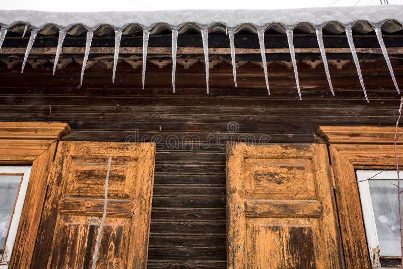 Icicle appese dal tetto di una casa di legno in campagna, in una giornata gelida e nuvolosa immagine stock libera da diritti