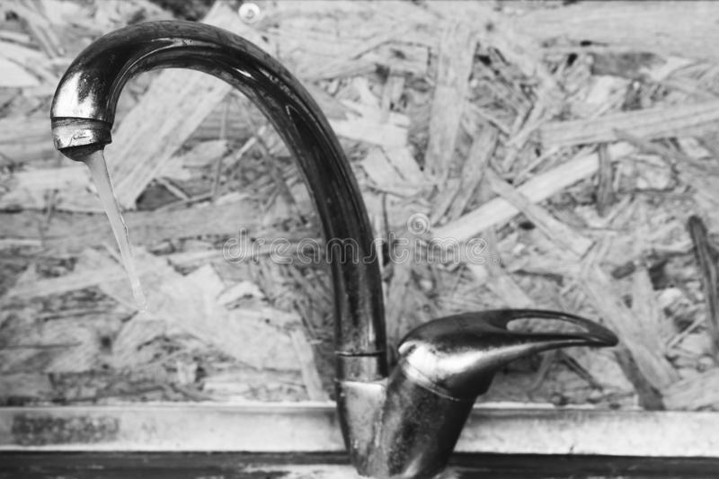 Icicle on the frozen water tap closeup indoors, selective focus. Black and white photo royalty free stock image