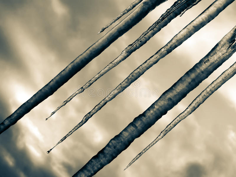 Icicles on a background of the cloudy sky. Diagonally. royalty free stock images