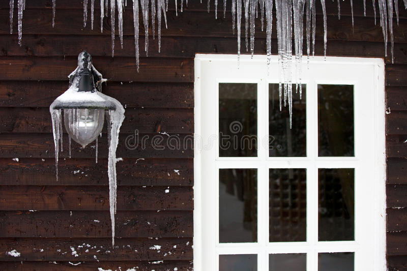 Icicles on the exterior of a panelled wooden house. Icicles hanging from a lamp on the exterior of a panelled wooden house with a white windowed door royalty free stock images