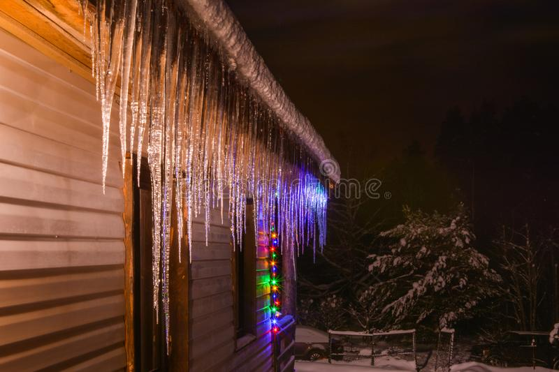 Icicles grow slowly in the cold winter. Bright lights of a garland illuminate icy tears of snow stock photos