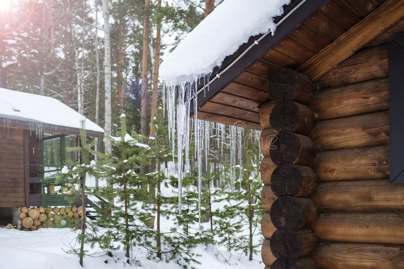 Icicles hang from the roof of a log house. stock photography