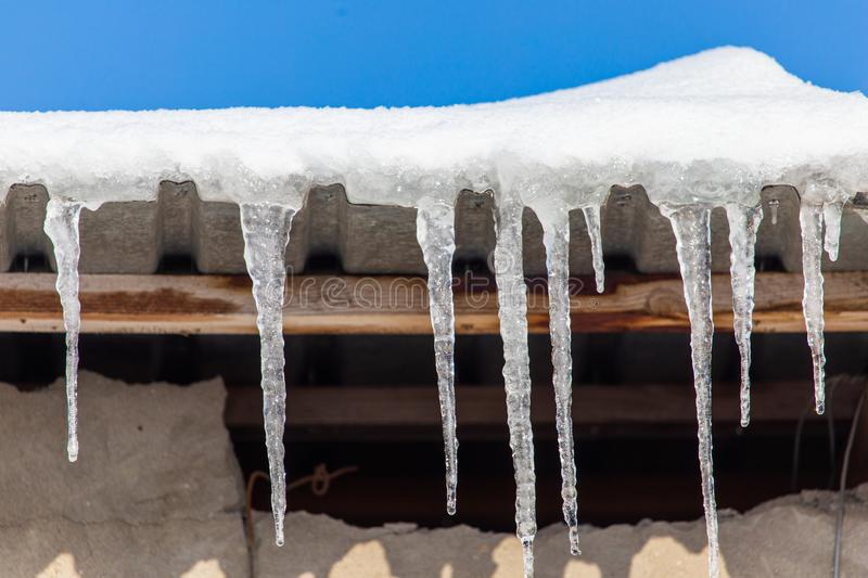 Icicles hang from the roof in winter royalty free stock photos