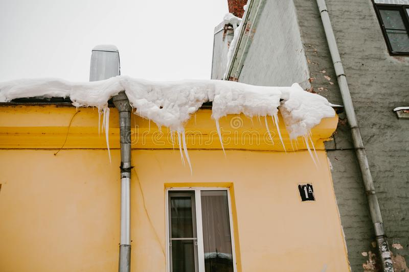 Icicles hang from the roof of a wooden house in the countryside, on a frosty cloudy day stock photography