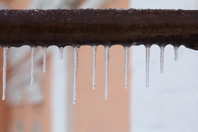 Icicles hanging from a brown pipe. Frozen water and metal surface, winter time concept. selective focus shallow depth of. Field photo stock image
