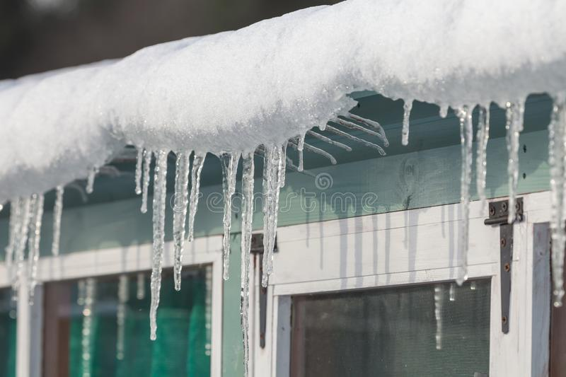 Icicles hanging from garden shed in winter stock photos