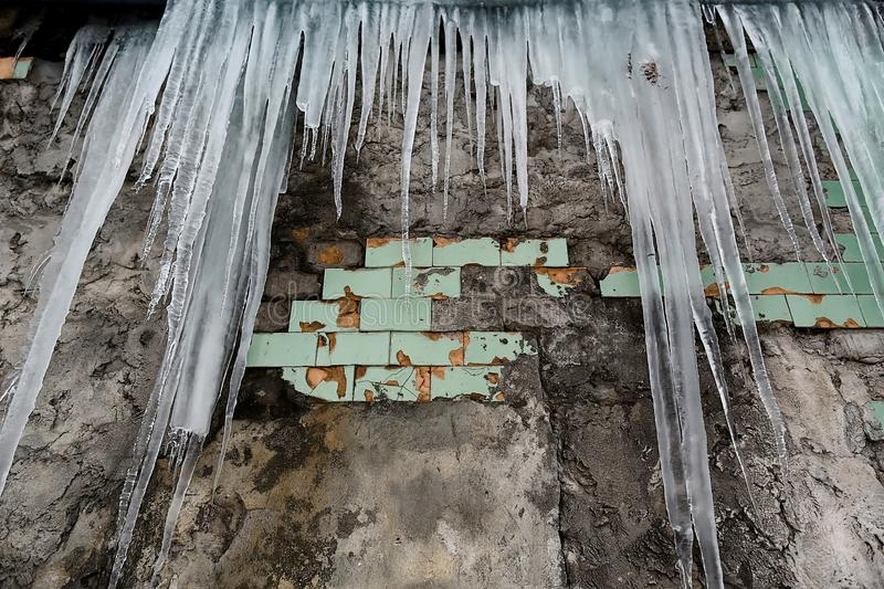 Icicles hanging from the roof of the old brick building with cubes of old tiles, traumatic acrid ice, thaw in the early spring, se. T stock photos