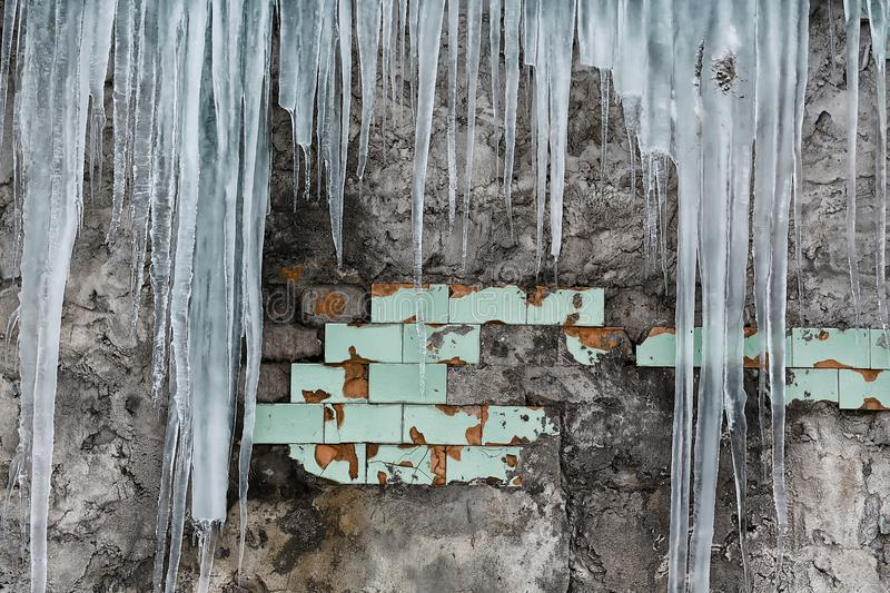 Icicles hanging from the roof of the old brick building with cubes of old tiles, traumatic acrid ice, thaw in the early spring, se. T royalty free stock photo
