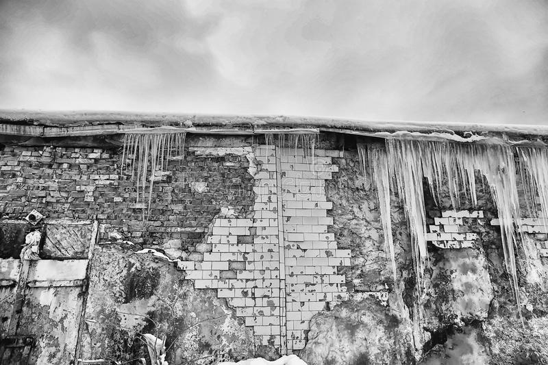 Icicles hanging from the roof of the old brick building with cubes of old tiles, traumatic acrid ice, thaw in the early spring, bl. Ack and white tone, set royalty free stock photo