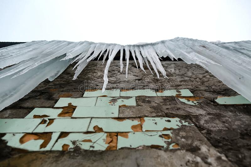 Icicles hanging from the roof of the old brick building with cubes of old tiles, traumatic acrid ice, thaw in the early spring, lo. Ok from below, set royalty free stock image