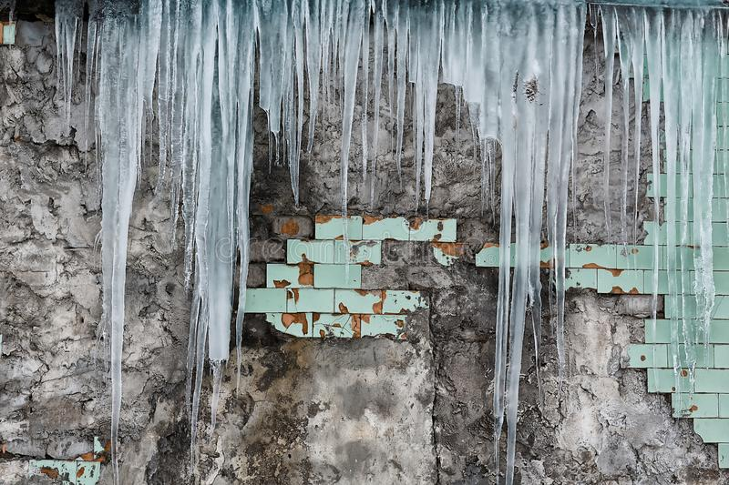 Icicles hanging from the roof of the old brick building with cubes of old tiles, traumatic acrid ice, thaw in the early spring, se. T stock photography