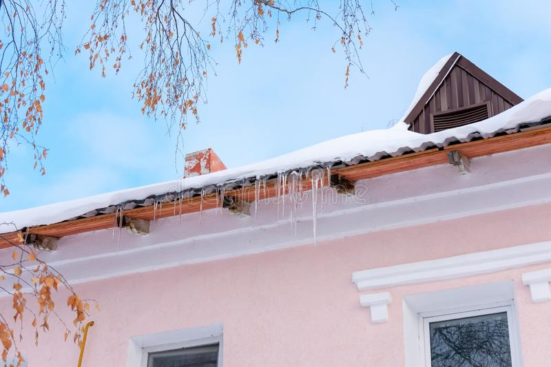 Icicles hanging on the roof of a pink building. Nice warm and Sunny weather stock photos