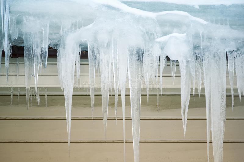 Icicles hanging on a roof stock photography
