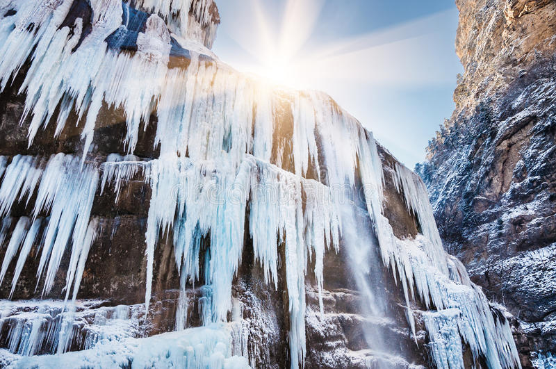 Icicles and a jet of water on the frozen waterfall stock photography