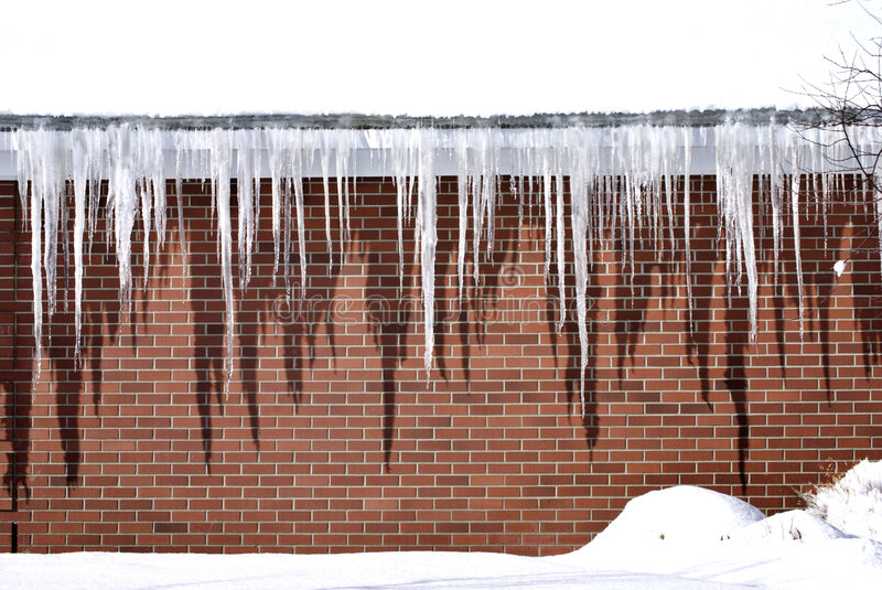Icicles overhanging a Brick Building. Long, sharp icicles overhanging a brick building wall, with pure white snow on the roof and on the ground stock image