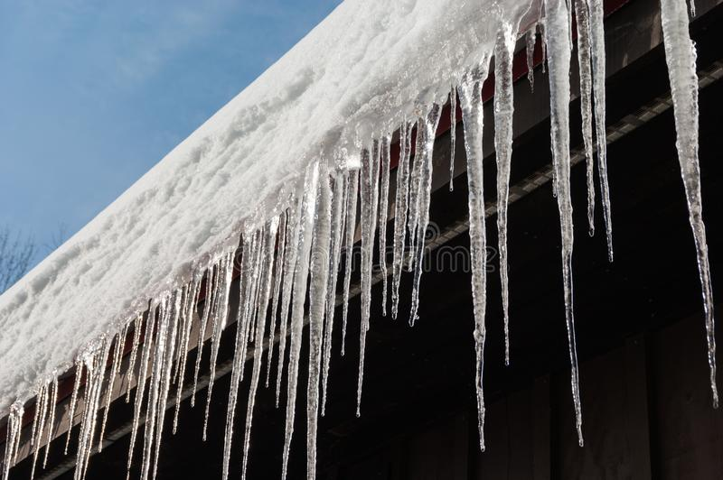 Icicles on roof in warm winter stock photos