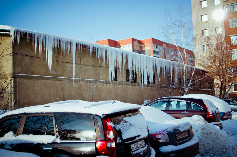 Icicles and snow-covered cars. royalty free stock photography
