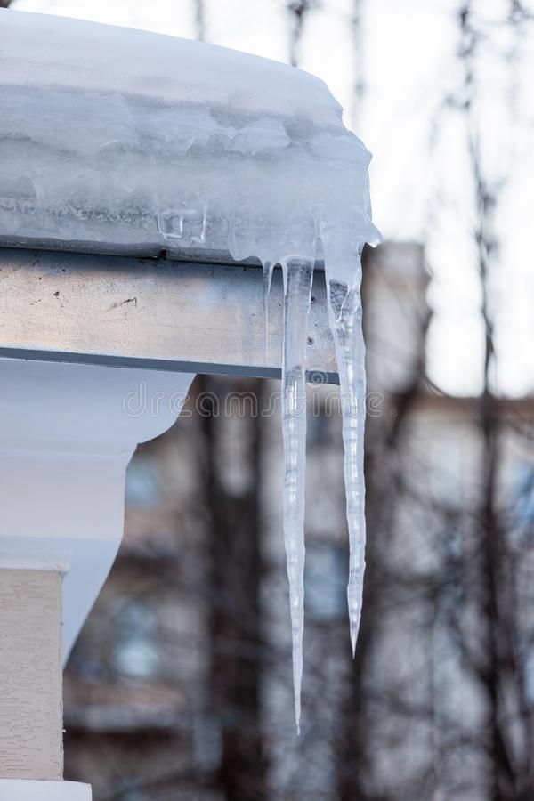 Icicles under the snow cap on the roof of the building in March at sunset stock images
