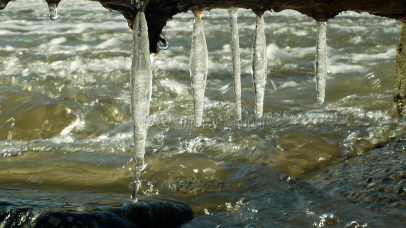 Icicles water river Morava in winter frozen magic and magical white, hanging from overhang, flowing down with ice stones royalty free stock image