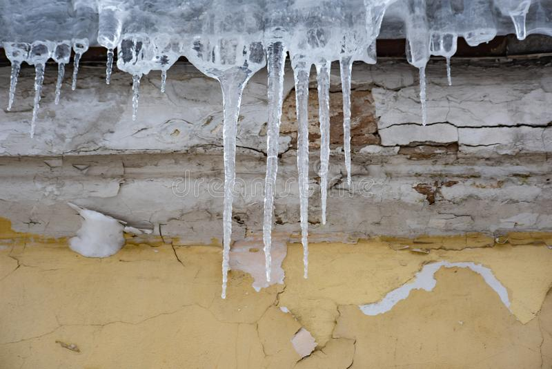 Icicles on the yellow ruined wall royalty free stock photo