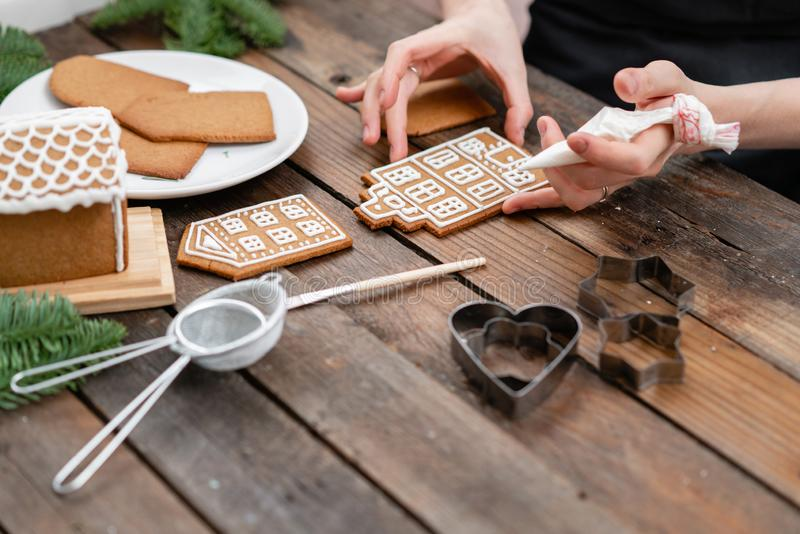 Icing of Christmas bakery. Woman decorating honey gingerbread cookies on wooden brown table. closeup, copy space. Blank. Biscuit gingerbread house, ready to stock photo