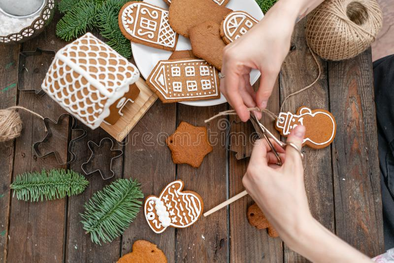 Icing of Christmas bakery. Woman decorating honey gingerbread cookies on wooden brown table. closeup, copy space. Blank. Biscuit gingerbread house, ready to royalty free stock photos