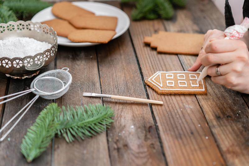 Icing of Christmas bakery. Woman decorating honey gingerbread cookies on wooden brown table. closeup, copy space. Blank. Biscuit gingerbread house, ready to royalty free stock image