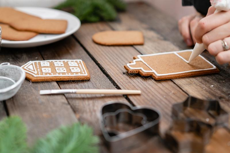 Icing of Christmas bakery. Woman decorating honey gingerbread cookies on wooden brown table. closeup, copy space. Blank. Biscuit gingerbread house, ready to royalty free stock images