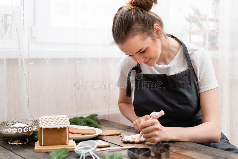Icing of Christmas bakery. Woman decorating honey gingerbread cookies on wooden brown table. closeup, copy space. Blank. Biscuit gingerbread house, ready to stock image
