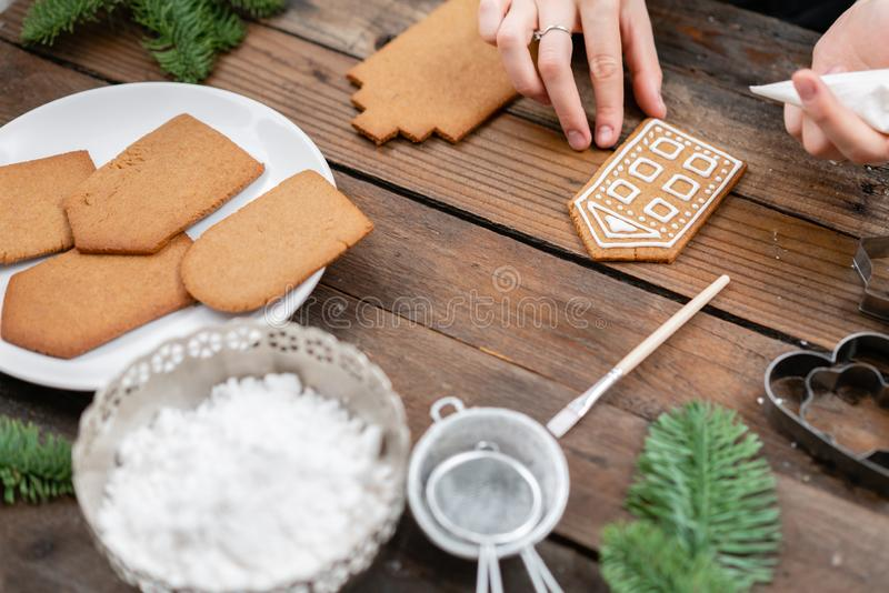 Icing of Christmas bakery. Woman decorating honey gingerbread cookies on wooden brown table. closeup, copy space. Blank. Biscuit gingerbread house, ready to royalty free stock photography