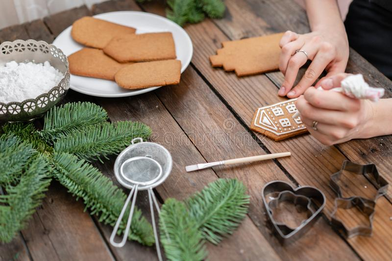Icing of Christmas bakery. Woman decorating honey gingerbread cookies on wooden brown table. closeup, copy space. Blank. Biscuit gingerbread house, ready to stock photos
