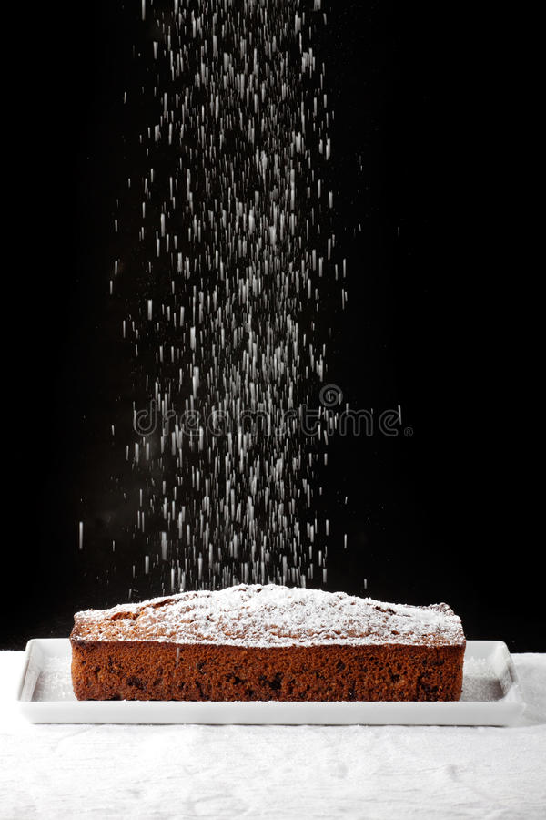 Icing sugar falling. On a chocolate cake royalty free stock image