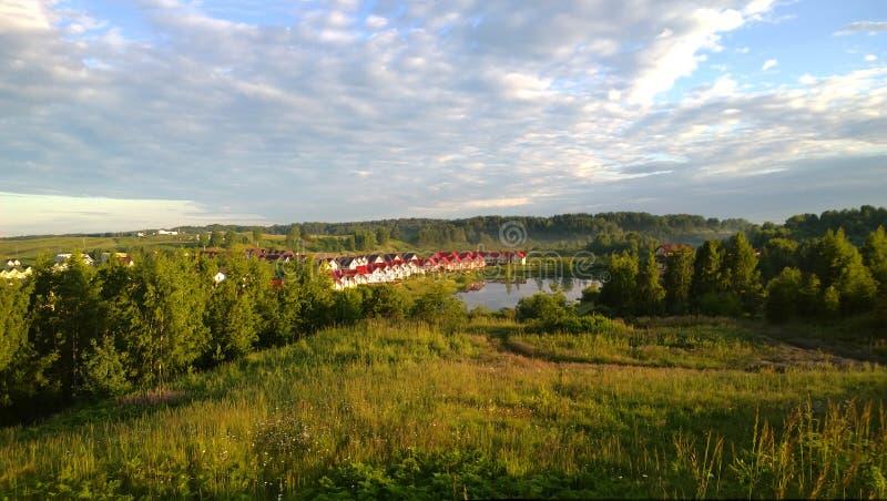 Icke-Urban landskap: fält, skog och en grupp av tanhouse i avståndet royaltyfria bilder