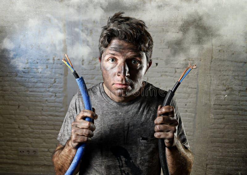 Icke-utbildad man som sammanfogar elektrisk kabel som lider elektrisk olycka med den smutsiga brända framsidan i roligt chockuttr arkivbilder