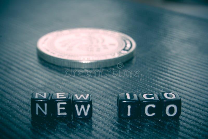 Ico novo das palavras de cubos pretos e de obscuridade da moeda de prata foto de stock royalty free