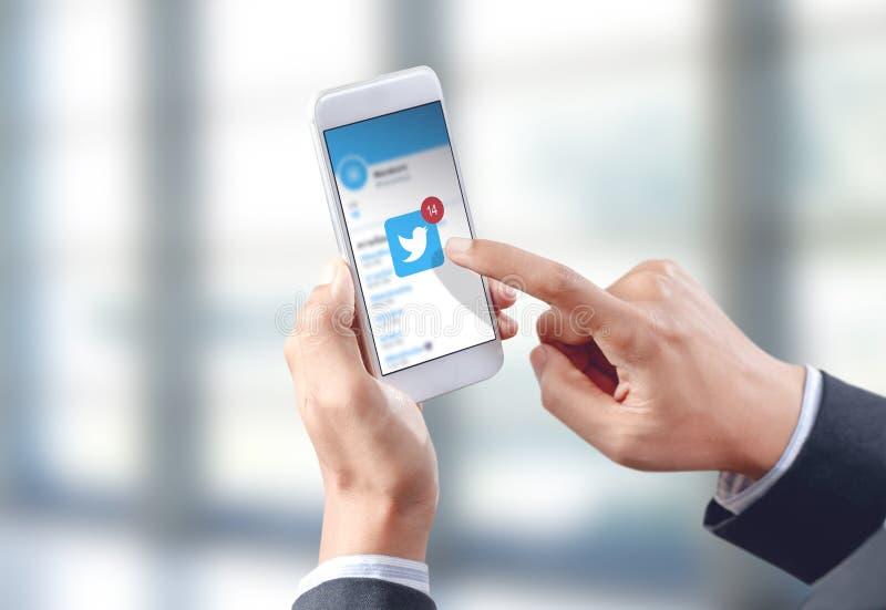 Icona del cinguettio di tocco della mano dell'uomo d'affari sullo schermo mobile fotografie stock